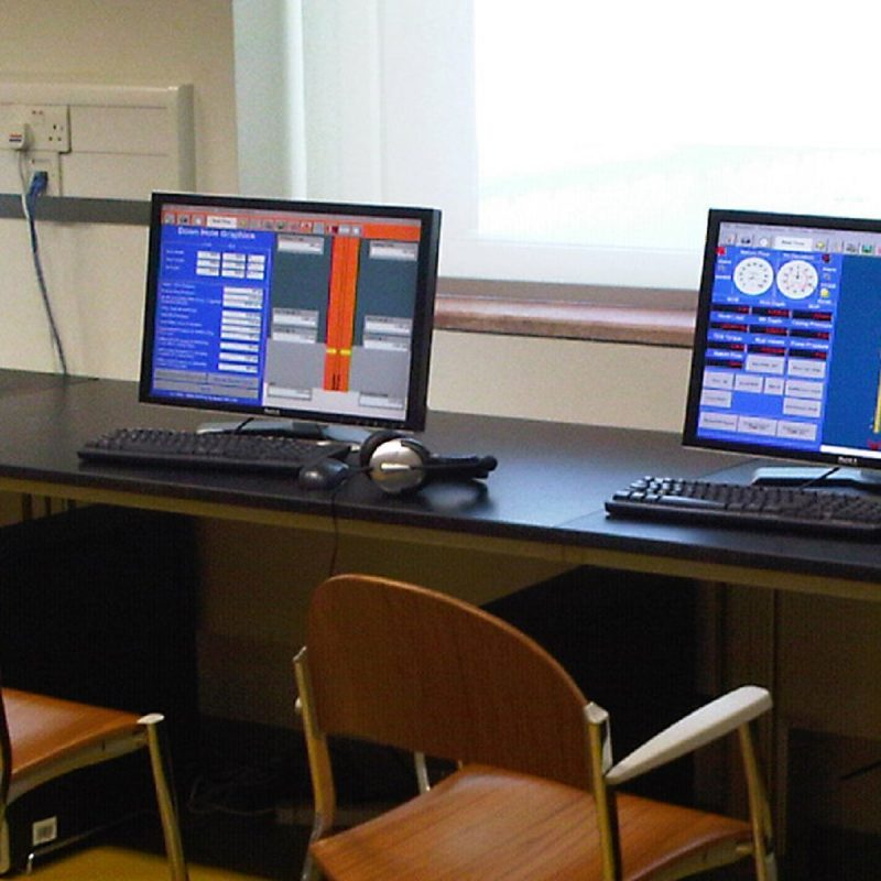 Two computer screens displaying the DrillSIM:5 software-based drilling and well control simulator consoles